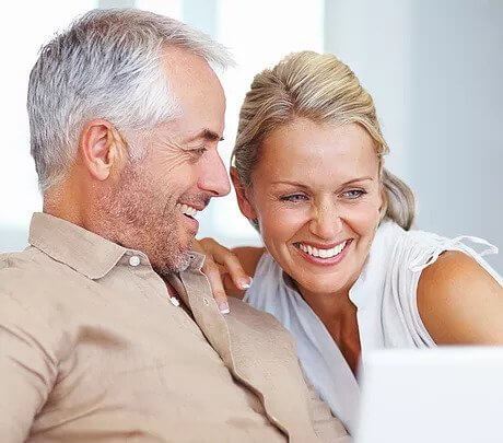 Middle-Age-Couple-Smiling at Test Results on Computer Screen