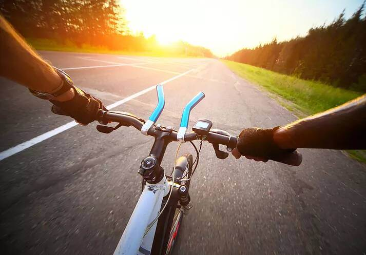 Riding Bicycle on Street into Sun